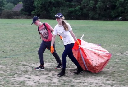 two young people dragging a large filled reg sack